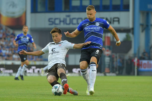 BIELEFELD, GERMANY - JULY 29: Ryo Miyaichi (L) of St. Pauli and Florian Hartherz of Bielefeld fight for the ball during the Second Bundesliga match between DSC Arminia Bielefeld and FC St. Pauli at Schueco Arena on July 29, 2019 in Bielefeld, Germany. (Photo by Thomas F. Starke/Bongarts/Getty Images)