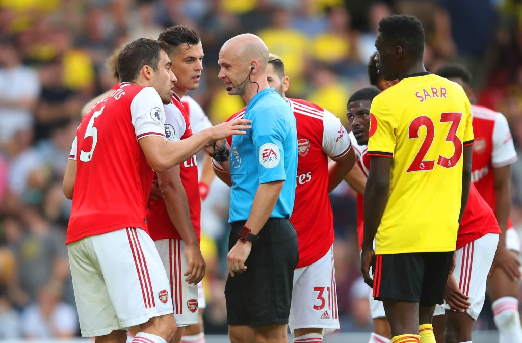 WATFORD, ENGLAND - SEPTEMBER 15: Granit Xhaka and Sokratis Papastathopoulos of Arsenal appeal to referee Anthony Taylor as he awards Watford a penalty during the Premier League match between Watford FC and Arsenal FC at Vicarage Road on September 15, 2019, in Watford, United Kingdom. (Photo by Marc Atkins/Getty Images)