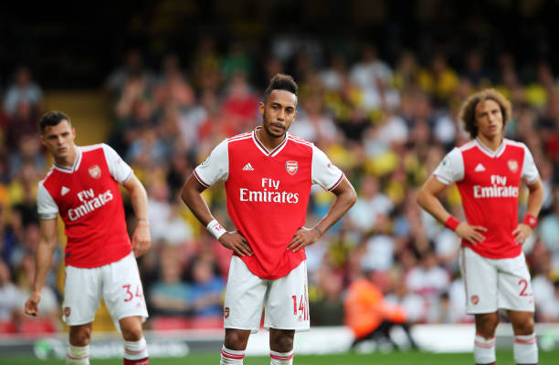 WATFORD, ENGLAND - SEPTEMBER 15: Pierre-Emerick Aubameyang of Arsenal (14) and team mates Granit Xhaka and David Luiz react during the Premier League match between Watford FC and Arsenal FC at Vicarage Road on September 15, 2019 in Watford, United Kingdom. (Photo by Marc Atkins/Getty Images)