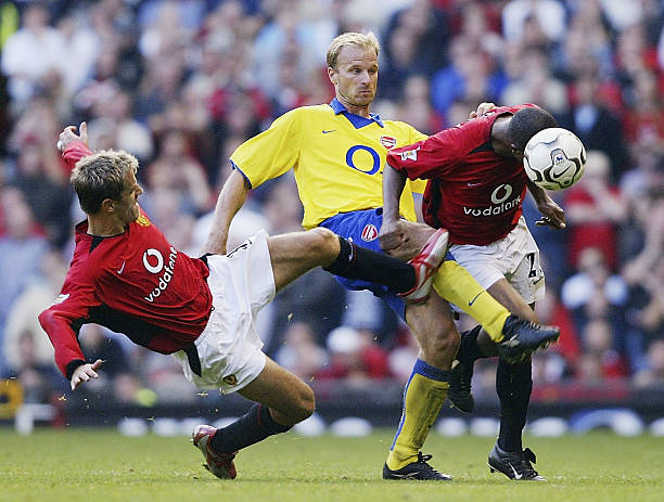 MANCHESTER, ENGLAND - SEPTEMBER 21:  Quinton Fortune and Phil Neville of Man Utd clash with Dennis Bergkamp of Arsenal during the FA Barclaycard Premiership match between Manchester United and Arsenal at Old Trafford on September 21, 2003 in Manchester, England. (Photo by Shaun Botterill/Getty Images)