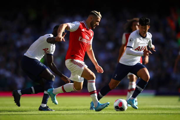 LONDON, ENGLAND - SEPTEMBER 01: Sead Kolasinac of Arsenal runs with the ball while pressured by Heung-Min Son of Tottenham Hotspur during the Premier League match between Arsenal FC and Tottenham Hotspur at Emirates Stadium on September 01, 2019 in London, United Kingdom. (Photo by Julian Finney/Getty Images)
