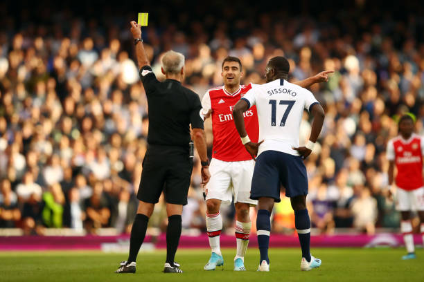 LONDON, ENGLAND - SEPTEMBER 01: Sokratis Papastathopoulos of Arsenal is shown a yellow card by referee Martin Atkinson during the Premier League match between Arsenal FC and Tottenham Hotspur at Emirates Stadium on September 01, 2019 in London, United Kingdom. (Photo by Julian Finney/Getty Images)