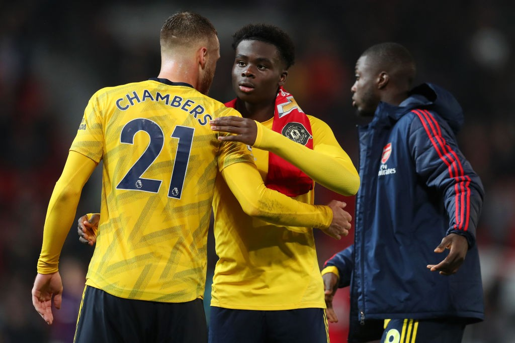 MANCHESTER, ENGLAND - SEPTEMBER 30: Bukayo Saka of Arsenal embraces Calum Chambers of Arsenal after the Premier League match between Manchester United and Arsenal FC at Old Trafford on September 30, 2019, in Manchester, United Kingdom. (Photo by Catherine Ivill/Getty Images)