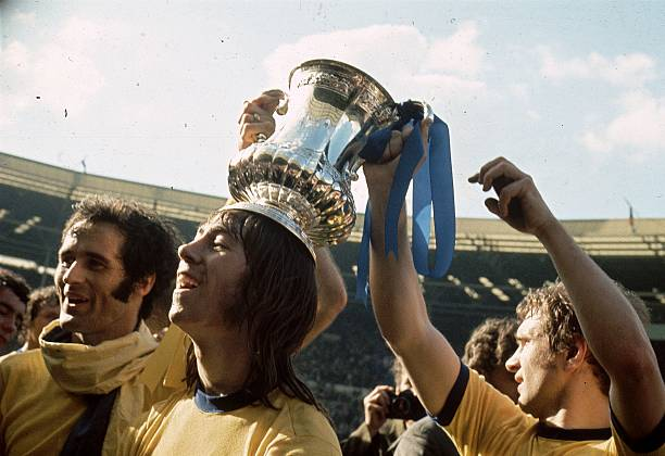 1971: Arsenal Football Club player Charlie George stands between George Graham and a fellow player who are holding the FA Cup on his head. (Photo by A. Jones/Express/Getty Images)