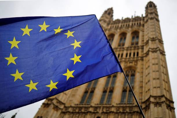 A European Union flag and belonging to an anti-Brexit activist flies outside the Houses of Parliament in London on October 23, 2019. - British Prime Minister Boris Johnson could pivot towards a general election as the EU mulls granting a Brexit deadline extension on Wednesday, after a fresh twist to the divorce saga cast doubt over his hopes of leaving on October 31. In tense parliamentary votes on Tuesday, Johnson won initial backing for the divorce deal he agreed with the EU -- but MPs then rejected his timetable to rush it through parliament in a matter of days. (Photo by Tolga Akmen / AFP)
