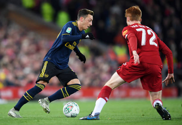 LIVERPOOL, ENGLAND - OCTOBER 30: Mesut Ozil of Arsenal is challenged by Sepp Van Den Berg of Liverpool during the Carabao Cup Round of 16 match between Liverpool and Arsenal at Anfield on October 30, 2019 in Liverpool, England. (Photo by Laurence Griffiths/Getty Images)