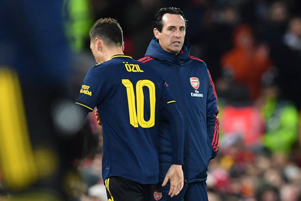 Arsenal's German midfielder Mesut Ozil (L) passes Arsenal's Spanish head coach Unai Emery as he leaves the pitch after being substituted off during the English League Cup fourth round football match between Liverpool and Arsenal at Anfield in Liverpool, north west England on October 30, 2019. (Photo by Paul ELLIS / AFP)