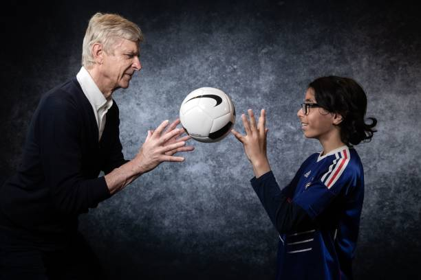 "Former Arsenal manager Arsene Wenger poses with Wazir, 13, during an event organized by ""Premiers de cordee"" association, whose aim is to help hospitalized children with sport, on May 22, 2019 at the Stade de France in Saint-Denis, northern France. (Photo by JOEL SAGET / AFP)"