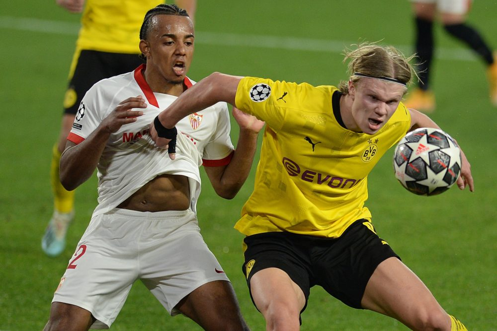 TOPSHOT - Dortmund's Norwegian forward Erling Braut Haaland (R) challenges Sevilla's French defender Jules Kounde during the UEFA Champions League round of 16 first leg football match between Sevilla FC and Borussia Dortmund at the Ramon Sanchez Pizjuan stadium in Seville on February 17, 2021. (Photo by CRISTINA QUICLER / AFP) (Photo by CRISTINA QUICLER/AFP via Getty Images)