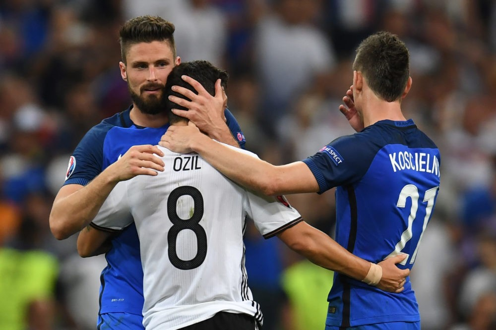 TOPSHOT - France's forward Olivier Giroud (L) and France's defender Laurent Koscielny (R) consol Germany's midfielder Mesut Oezil after France beat Germany 2-0 in the Euro 2016 semi-final football match between Germany and France at the Stade Velodrome in Marseille on July 7, 2016. France will face Portugal in the finals on July 10, 2016. / AFP / PATRIK STOLLARZ