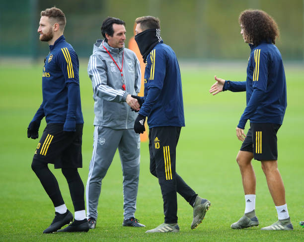 ST ALBANS, ENGLAND - NOVEMBER 27:  Unai Emery, Manager of Arsenal shakes hands with Mesut Ozil and team mates Shkodran Mustafi and Matteo Guendouzi during an Arsenal training session on the eve of their UEFA Europa League match against Eintracht Frankfurt at London Colney on November 27, 2019 in St Albans, England. (Photo by Warren Little/Getty Images)