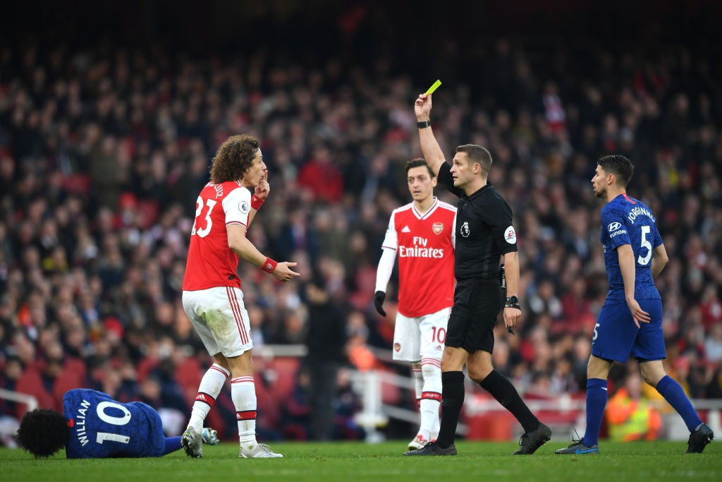LONDON, ENGLAND - DECEMBER 29: Referee Craig Pawson shows a yellow card to David Luiz of Arsenal during the Premier League match between Arsenal FC and Chelsea FC at Emirates Stadium on December 29, 2019, in London, United Kingdom. (Photo by Shaun Botterill/Getty Images)