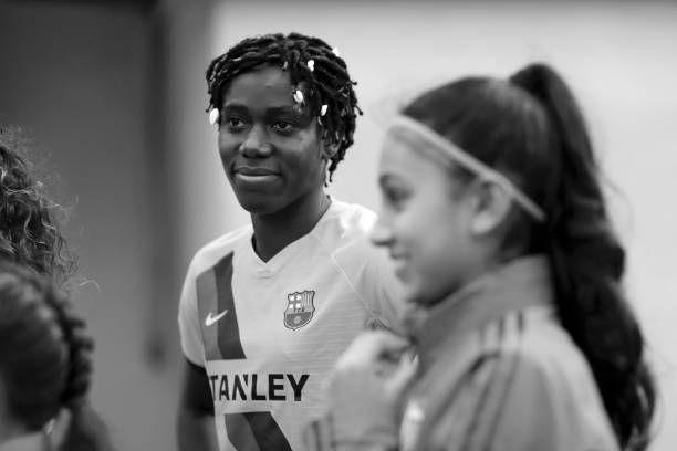BOREHAMWOOD, ENGLAND - AUGUST 14: (EDITORS NOTE: Image has been converted to black and white.) Asisat Oshoala of Barcelona speaks to a match day mascot ahead of the Pre Season Friendly match between Arsenal and Barcelona at Meadow Park on August 14, 2019 in Borehamwood, England. (Photo by Naomi Baker/Getty Images)