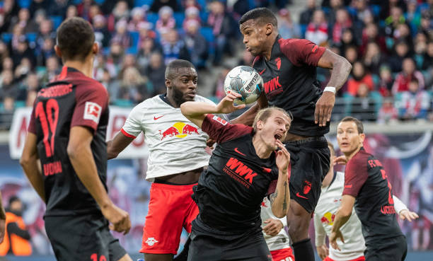 LEIPZIG, GERMANY - DECEMBER 21: Dayot Upamecano of RB Leipzig jumps for a header with Tin Jedvaj and Sergio Cordova of FC Augsburg during the Bundesliga match between RB Leipzig and FC Augsburg at Red Bull Arena on December 21, 2019 in Leipzig, Germany. (Photo by Boris Streubel/Bongarts/Getty Images)