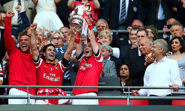 LONDON, ENGLAND - MAY 17: Captain Thomas Vermaelen of Arsenal (2R) lifts the trophy in celebration alongside Lukas Podolski (L), Mikel Arteta (2L) and Arsene Wenger manager of Arsenal (R) after the FA Cup with Budweiser Final match between Arsenal and Hull City at Wembley Stadium on May 17, 2014 in London, England. (Photo by Clive Mason/Getty Images)