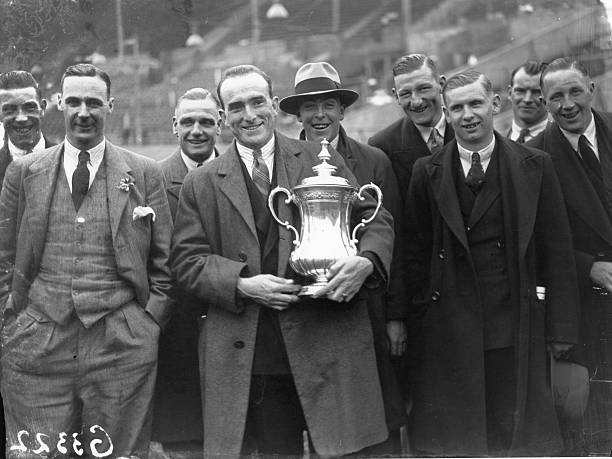 24th April 1930: The triumphant players of Arsenal FC with the FA Cup trophy after 2-0 victory over Huddersfield Town at Wembley Stadium. Tom Parker holds the trophy. (Photo by J. Gaiger/Topical Press Agency/Getty Images)