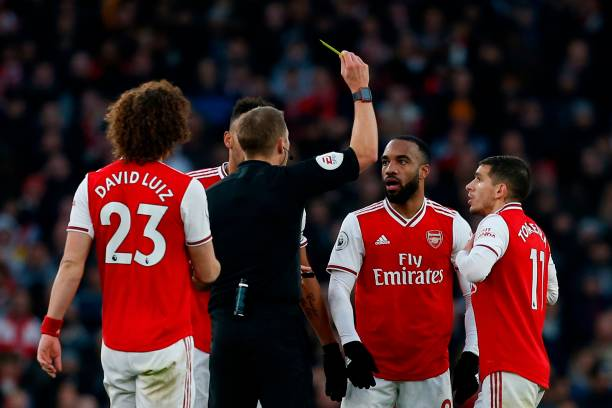Arsenal's French striker Alexandre Lacazette (2R) is shown a yellow card by referee Craig Pawson during the English Premier League football match between Arsenal and Chelsea at the Emirates Stadium in London on December 29, 2019. (Photo by Ian KINGTON / IKIMAGES / AFP) / RESTRICTED TO EDITORIAL USE. No use with unauthorized audio, video, data, fixture lists, club/league logos or 'live' services. Online in-match use limited to 45 images, no video emulation. No use in betting, games or single club/league/player publications. (Photo by IAN KINGTON/IKIMAGES/AFP via Getty Images)