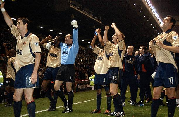 MANCHESTER, UNITED KINGDOM: Arsenal players (L-R:) Martin Keown, captain Patrick Vieira,keeper David Seaman, Ashley Cole,Ray Parlour, and Edu celebrate after a premier league match win over Manchester United at Old Trafford 08 May 2002. The win secured Arsenal the double after winning the cup final 04 May 2002. (Photo credit PAUL BARKER/AFP via Getty Images)
