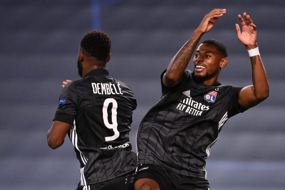 Lyon's French forward Moussa Dembele (L) celebrates with Lyon's French midfielder Jeff Reine-Adelaide after scoring his second goal during the UEFA Champions League quarter-final football match between Manchester City and Lyon at the Jose Alvalade stadium in Lisbon on August 15, 2020. (Photo by FRANCK FIFE / POOL / AFP)