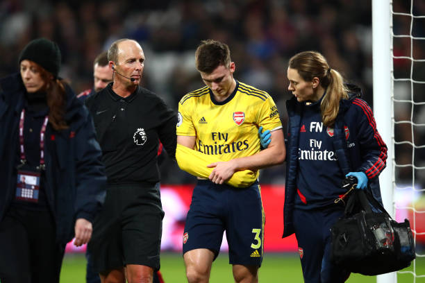LONDON, ENGLAND - DECEMBER 09: Referee Mike Dean helps Kieran Tierney of Arsenal leave the pitch following an injury during the Premier League match between West Ham United and Arsenal FC at London Stadium on December 09, 2019 in London, United Kingdom. (Photo by Julian Finney/Getty Images)
