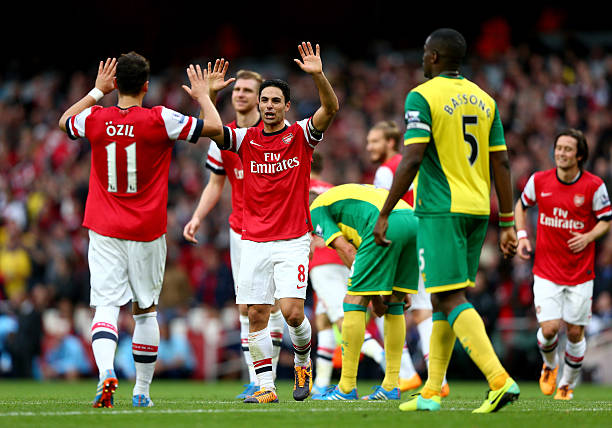 LONDON, ENGLAND - OCTOBER 19: Mesut Oezil of Arsenal (11) celebrates with Mikel Arteta as he scores their fourth goal during the Barclays Premier League match between Arsenal and Norwich City at Emirates Stadium on October 19, 2013 in London, England. (Photo by Paul Gilham/Getty Images)