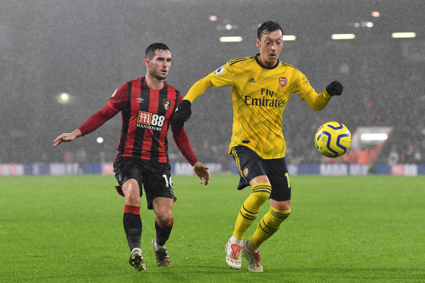BOURNEMOUTH, ENGLAND - DECEMBER 26: Mesut Ozil of Arsenal battles for possession with Lewis Cook of AFC Bournemouth during the Premier League match between AFC Bournemouth and Arsenal FC at Vitality Stadium on December 26, 2019 in Bournemouth, United Kingdom. (Photo by Justin Setterfield/Getty Images)