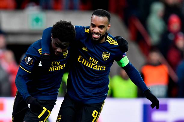 Arsenal's English striker Bukayo Saka (L) celebrates with Arsenal's French striker Alexandre Lacazette after scoring during the UEFA Europa League Group F football match between R. Standard de Liege and Arsenal FC at the Maurice Dufrasne Stadium in Sclessin on December 12, 2019. (Photo by JOHN THYS / AFP)