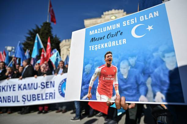 "A supporter of China's Muslim Uighur minority holds a placard of Arsenal's Turkish origin German midfielder Mesut Ozil reading ""Thanks for being our voice"" past flags of East Turkestan during a demonstration at Beyazid square in Istanbul on December 14, 2019. - Arsenal's Mesut Ozil, a German footballer of Turkish origin, expressed on December 14, 2019 support for Uighurs in Xinjiang and criticised Muslim countries for their failure to speak up for them. (Photo by Ozan KOSE / AFP) (Photo by OZAN KOSE/AFP via Getty Images)"