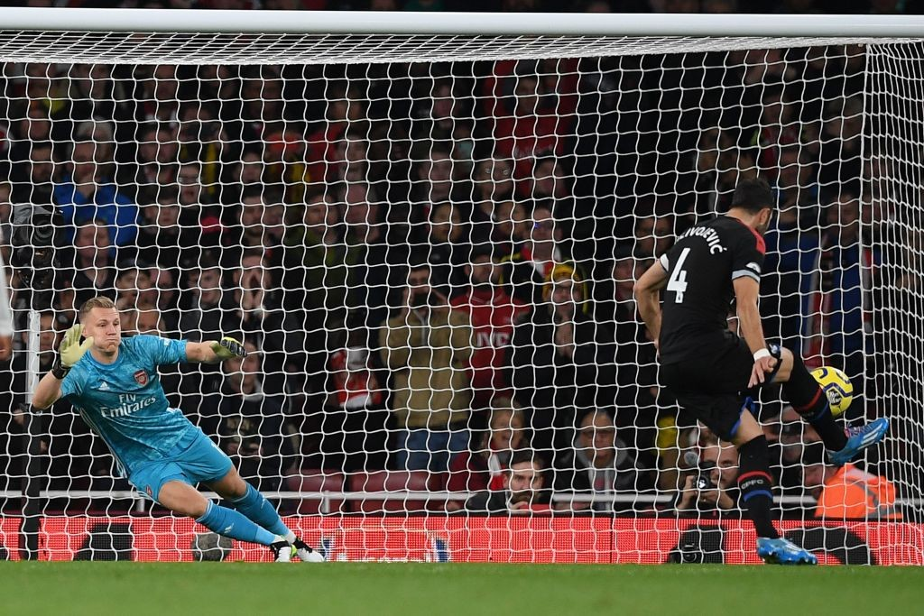 Crystal Palace's Serbian midfielder Luka Milivojevic (R) scores their first goal past Arsenal's German goalkeeper Bernd Leno (L) from the penalty spot during the English Premier League football match between Arsenal and Crystal Palace at the Emirates Stadium in London on October 27, 2019. (Photo by DANIEL LEAL-OLIVAS / AFP)