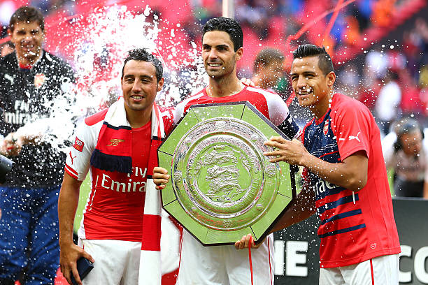 LONDON, ENGLAND - AUGUST 10: (L-R) Santi Cazorla, Mikel Arteta and Alexis Sanchez of Arsenal pose with the trophy after the FA Community Shield match between Manchester City and Arsenal at Wembley Stadium on August 10, 2014 in London, England. (Photo by Clive Mason/Getty Images)