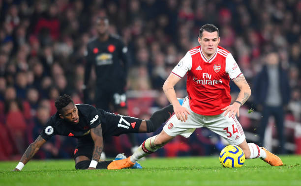 LONDON, ENGLAND - JANUARY 01: Granit Xhaka of Arsenal is challenged by Fred of Manchester United during the Premier League match between Arsenal FC and Manchester United at Emirates Stadium on January 01, 2020 in London, United Kingdom. (Photo by Clive Mason/Getty Images)