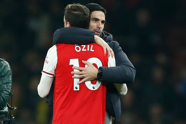 Arsenal's Spanish head coach Mikel Arteta (R) embraces Arsenal's German midfielder Mesut Ozil (L) on the pitch after the English Premier League football match between Arsenal and Manchester United at the Emirates Stadium in London on January 1, 2020. - Arsenal won the game 2-0. (Photo by Ian KINGTON / IKIMAGES / AFP)