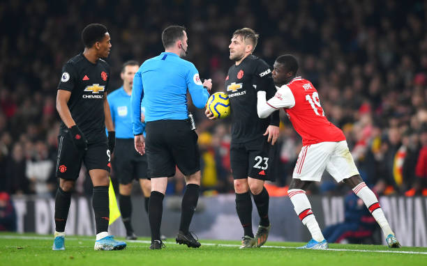 LONDON, ENGLAND - JANUARY 01: Nicolas Pepe of Arsenal pushes Luke Shaw of Manchester United as referee Chris Kavanagh speaks to them both during the Premier League match between Arsenal FC and Manchester United at Emirates Stadium on January 01, 2020 in London, United Kingdom. (Photo by Clive Mason/Getty Images)