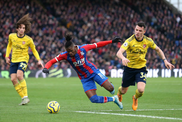 LONDON, ENGLAND - JANUARY 11: Wilfried Zaha of Crystal Palace battles for possession with Granit Xhaka of Arsenal during the Premier League match between Crystal Palace and Arsenal FC at Selhurst Park on January 11, 2020 in London, United Kingdom. (Photo by Alex Pantling/Getty Images)