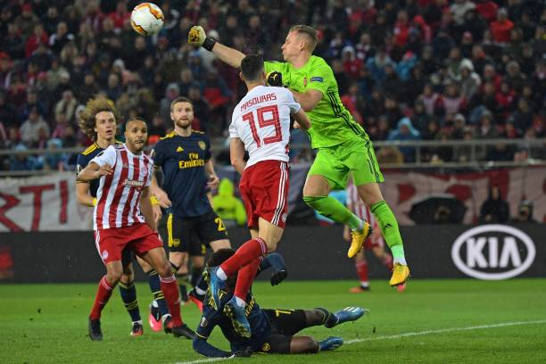 Arsenal's German goalkeeper Bernd Leno (R) punches the ball clear during the UEFA Europa League round of 32 first leg football match between Olympiakos and Arsenal at the Karaiskakis Stadium in Piraeus, near Athens, on February 20, 2020.