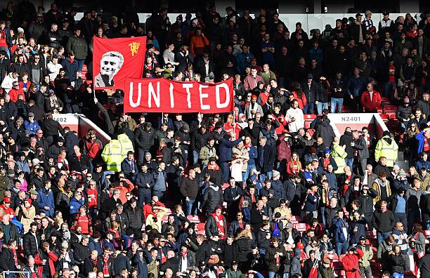 Manchester United fans hold a banner depicting Manchester United's Portuguese manager Jose Mourinho ahead of the English Premier League football match between Manchester United and Arsenal at Old Trafford in Manchester, north west England, on November 19, 2016.