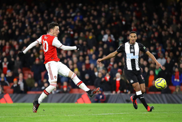 Mesut Ozil of Arsenal scores his sides third goal during the Premier League match between Arsenal FC and Newcastle United at Emirates Stadium on February 16, 2020 in London, United Kingdom.