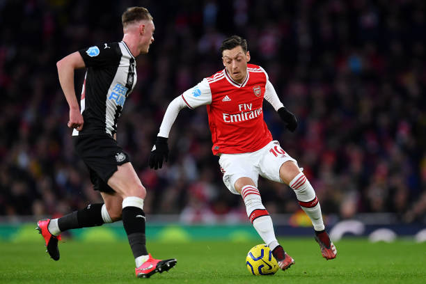 Mesut Ozil of Arsenal takes on Sean Longstaff of Newcastle United during the Premier League match between Arsenal FC and Newcastle United at Emirates Stadium on February 16, 2020 in London, United Kingdom.