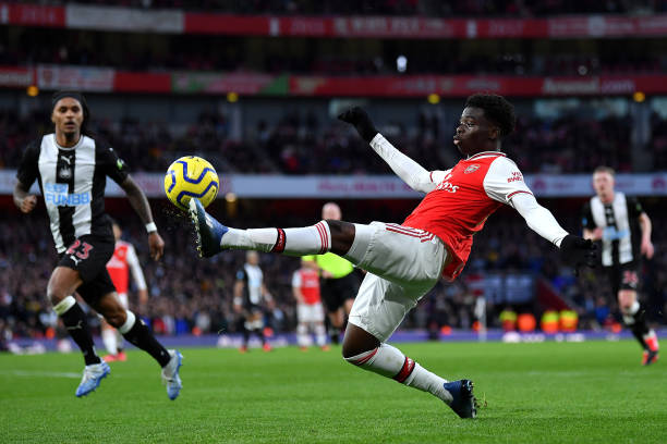 Bukayo Saka of Arsenal stretches for the ball during the Premier League match between Arsenal FC and Newcastle United at Emirates Stadium on February 16, 2020 in London, United Kingdom.