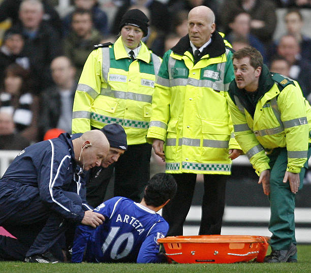 A medic (R) signals an injury to the leg of Everton's Spanish player Mikel Arteta (Below) during a Premier League football match against Newcastle at St James' Park in Newcastle, on February 22, 2009. AFP PHOTO/IAN KINGTON