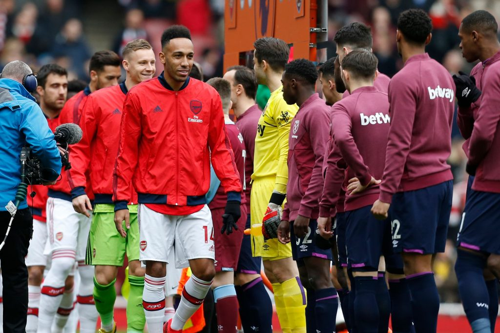 Arsenal players, led by Arsenal's Gabonese striker Pierre-Emerick Aubameyang (centre right) walk past West Ham players instead of the usual handshakes before the English Premier League football match between Arsenal and West Ham at the Emirates Stadium in London on March 7, 2020.