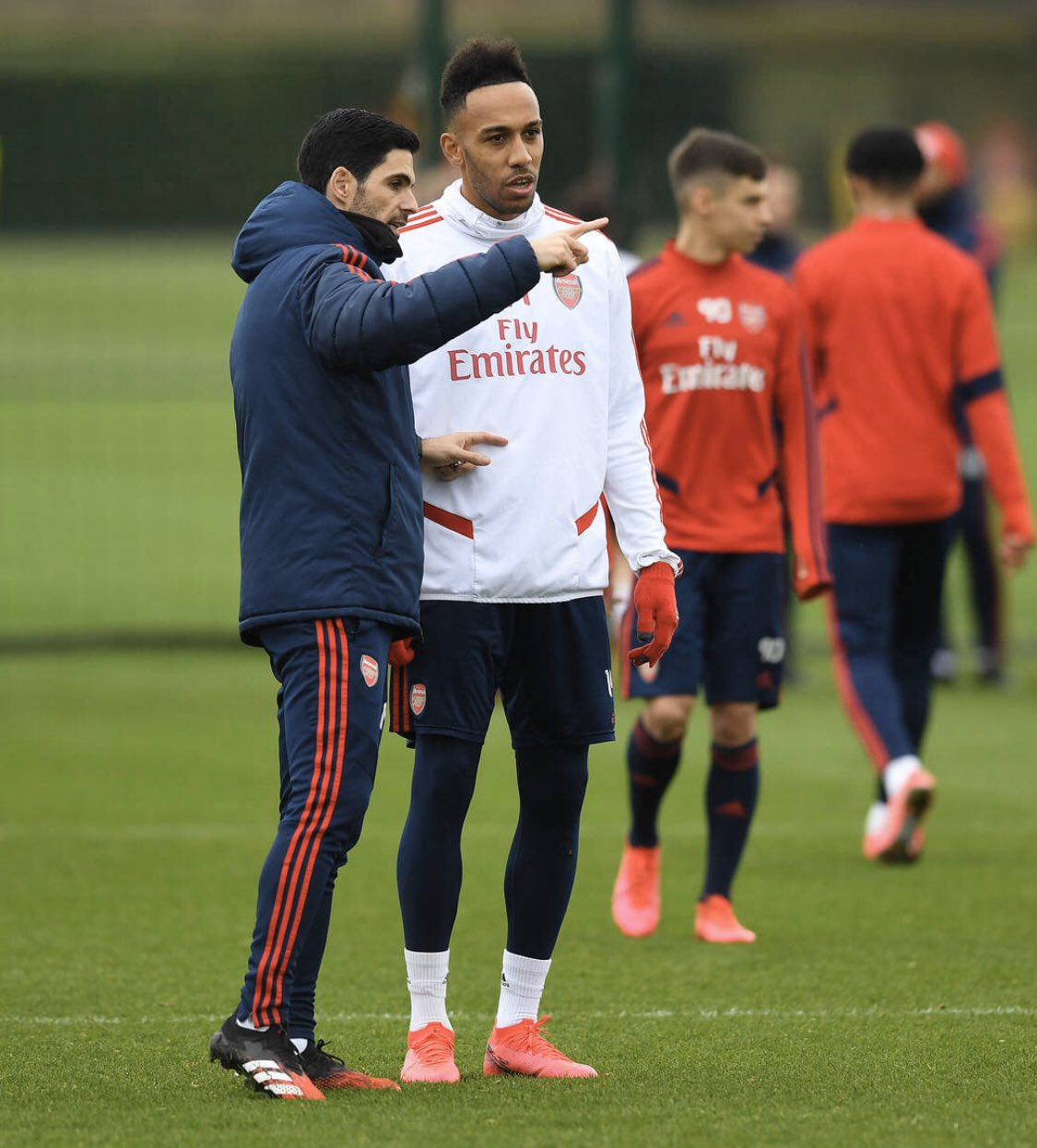 Mikel Arteta and Pierre-Emerick Aubameyang speak in the foreground, with Catalin Cirjan behind them. Triallist Tyger Smalls walks away in the background (Photo via Tyger Smalls on Twitter)
