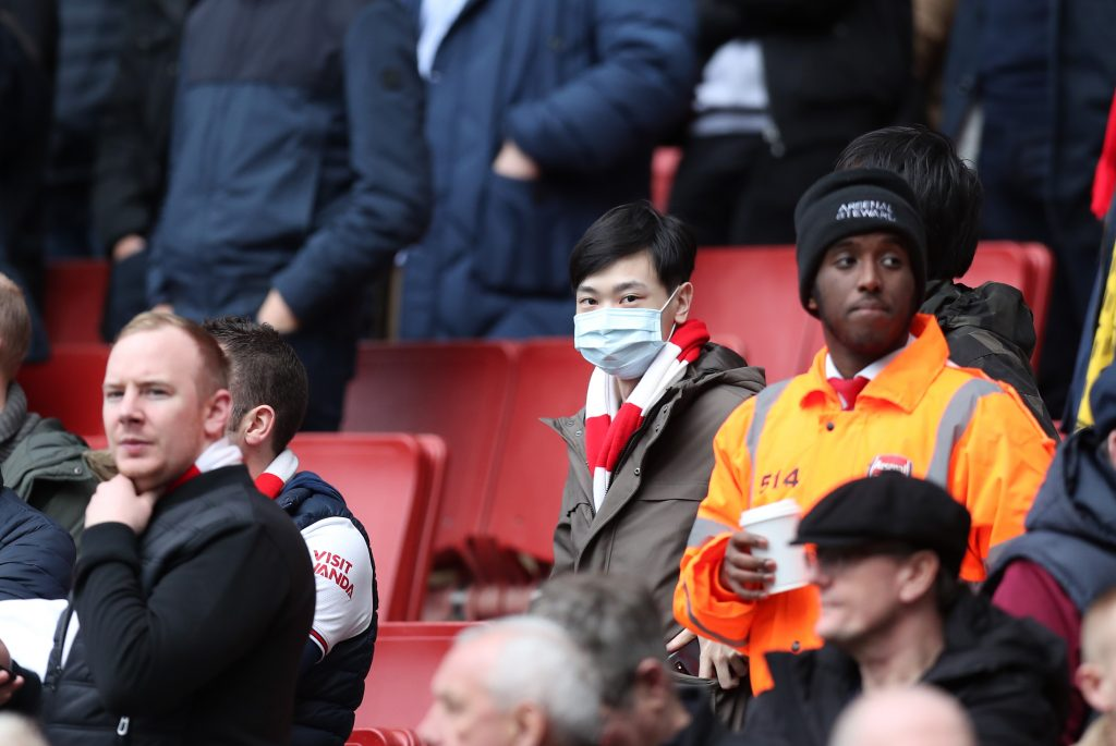 A fan wears a disposable face mask during the Premier League match between Arsenal FC and West Ham United at Emirates Stadium on March 07, 2020 in London, United Kingdom.