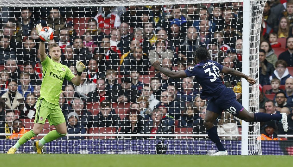 Arsenal's German goalkeeper Bernd Leno (L) makes a save from West Ham United's English midfielder Michail Antonio (R) during the English Premier League football match between Arsenal and West Ham at the Emirates Stadium in London on March 7, 2020.
