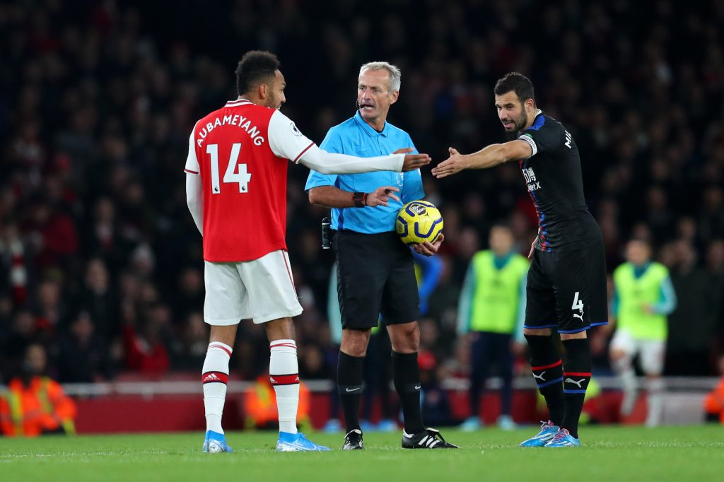 Referee Martin Atkinson speaks with Pierre-Emerick Aubameyang of Arsenal and Luka Milivojevic of Crystal Palace during the Premier League match between Arsenal FC and Crystal Palace at Emirates Stadium on October 27, 2019 in London, United Kingdom.
