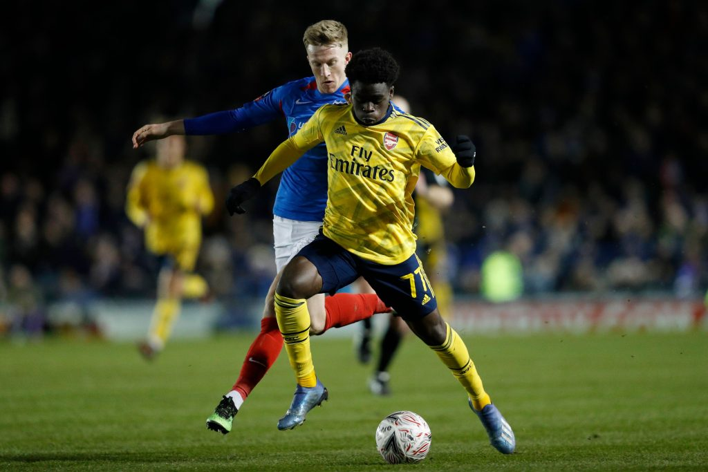 Arsenal's English striker Bukayo Saka (R) runs with the ball during the English FA Cup fifth round football match between Portsmouth and Arsenal at Fratton Park stadium in Portsmouth, southern England, on March 2, 2020.