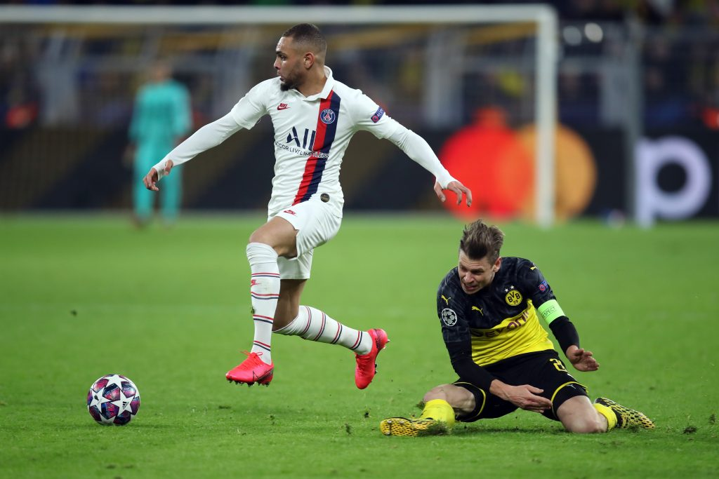 DORTMUND, GERMANY - FEBRUARY 18: Lukas Piszczek of Dortmund is challenged by Layvin Kurzawa of Paris Saint-Germain during the UEFA Champions League round of 16 first leg match between Borussia Dortmund and Paris Saint-Germain at Signal Iduna Park on February 18, 2020, in Dortmund, Germany. (Photo by Alex Grimm/Getty Images)