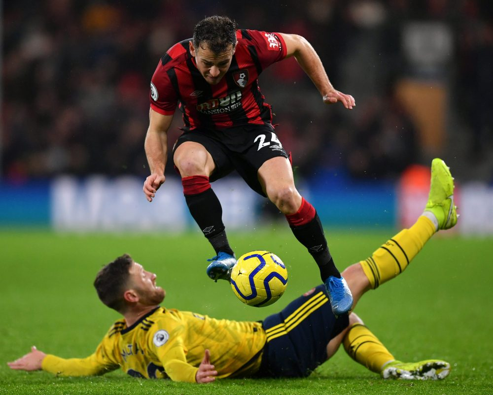 BOURNEMOUTH, ENGLAND - DECEMBER 26: Ryan Fraser of AFC Bournemouth jumps past a tackle from Shkodran Mustafi of Arsenal during the Premier League match between AFC Bournemouth and Arsenal FC at Vitality Stadium on December 26, 2019 in Bournemouth, United Kingdom. (Photo by Dan Mullan/Getty Images)