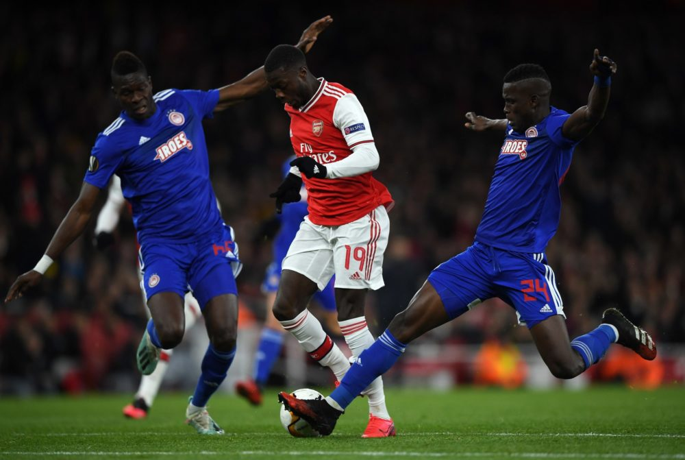 LONDON, ENGLAND - FEBRUARY 27: Nicolas Pepe of Arsenal FC is tackled by Pape Abou Cisse and Ousseynou Ba of Olympiacos FC during the UEFA Europa League round of 32 second leg match between Arsenal FC and Olympiacos FC at Emirates Stadium on February 27, 2020 in London, United Kingdom. (Photo by Mike Hewitt/Getty Images)