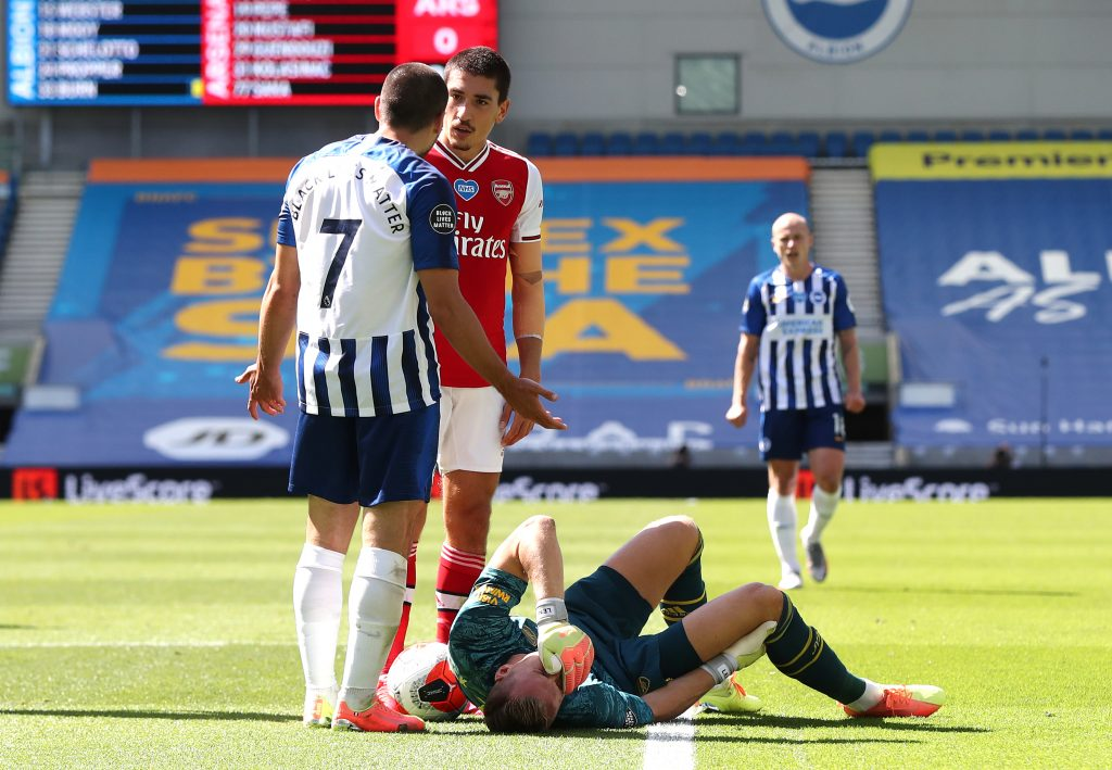 BRIGHTON, ENGLAND - JUNE 20: Bernd Leno of Arsenal goes down injured and in pain as Neal Maupay of Brighton and Hove Albion argues with Hector Bellerin of Arsenal during the Premier League match between Brighton & Hove Albion and Arsenal FC at American Express Community Stadium on June 20, 2020 in Brighton, England. Football Stadiums around Europe remain empty due to the Coronavirus Pandemic as Government social distancing laws prohibit fans inside venues resulting in all fixtures being played behind closed doors. (Photo by Gareth Fuller/Pool via Getty Images)